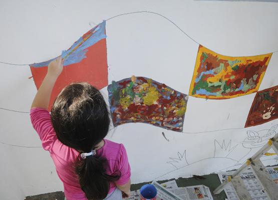 Foto: Criança capricha na pintura do desenho na parede | Crédito: Rogério Capela
